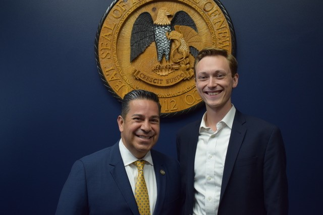 Assistant Speaker of the House Ben Ray Luján with Tomas Wesley Green in front of the seal of New Mexico