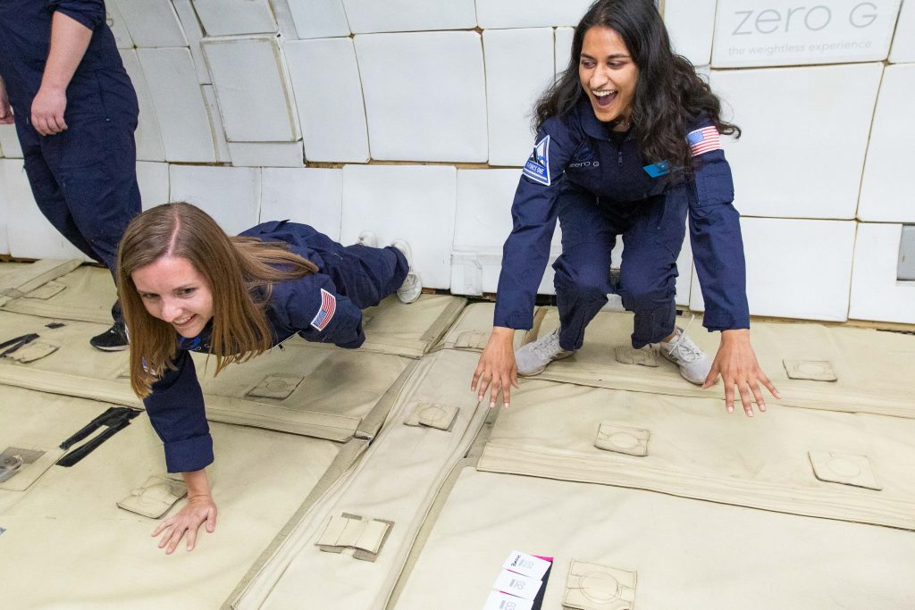 Becca Browder (l) does a one-armed push-up while helping Media Lab's Mehak Sarang with an experiment aboard a lunar gravity flight. Photo: Steve Boxall/ZERO-G